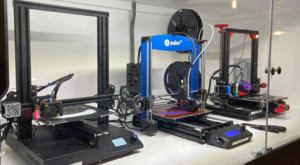 Three of DJMs 3D Printers behind glass
