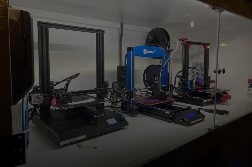 Three 3D Printers inside glass case