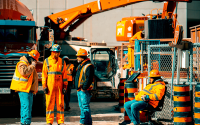 four construction workers talking in front of equipment